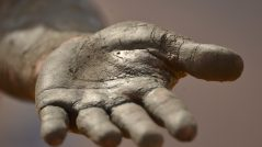 Faça com que as pessoas dependam de você: Imagem de uma mão estendida suja de barro